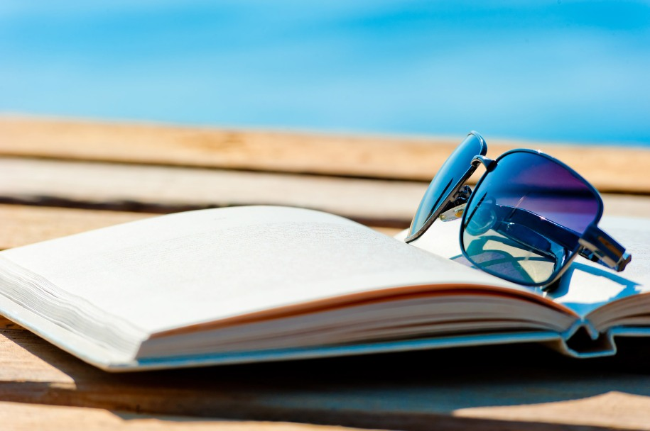 open book and sunglasses on the background of the sea